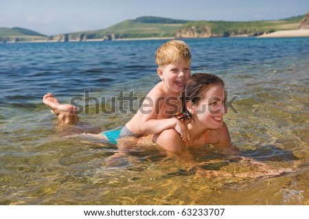 happy family of mother with kid playing  in the sea waves - stock photo