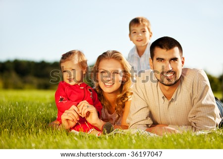 Happy family of 4 people lying on grass under summer sun. Focus is on the man. - stock photo