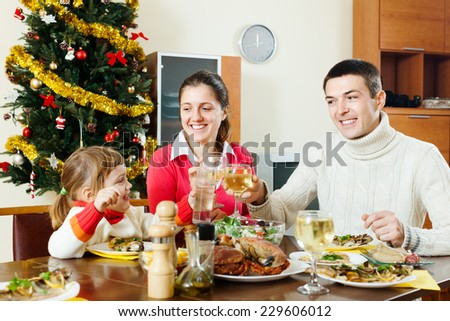 Happy family of three celebrating Christmas over  table  - stock photo