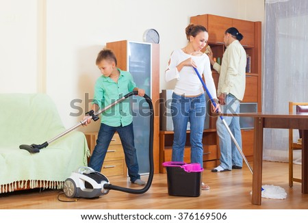 Happy family of three doing housework together
