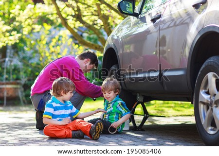 Happy family of three: father and two little boys repairing car and changing wheel together on warm day, outdoors.