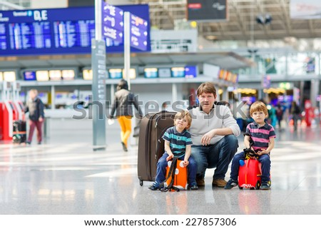 Happy family of three: Father and two little kid boys at the international big airport, traveling together and going on summer journey. - stock photo
