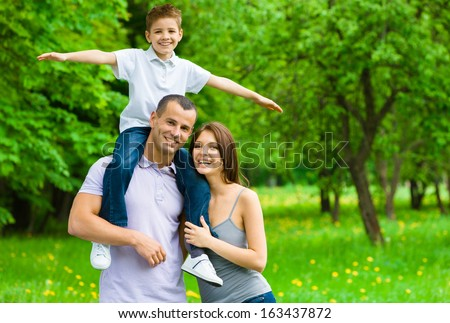 Happy family of three. Father keeps son airplane gesturing on shoulders. Concept of happy family relations and carefree leisure time - stock photo