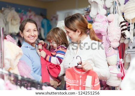 Happy family of three generations chooses wear at children's clothes shop - stock photo
