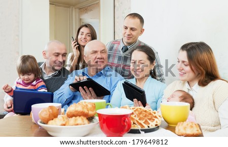 Happy family of three generations or group of friends with electronic devices over tea in living room at home
