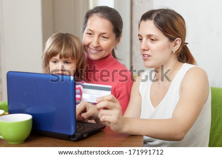 Happy family of three generations shopping online in living room at home - stock photo