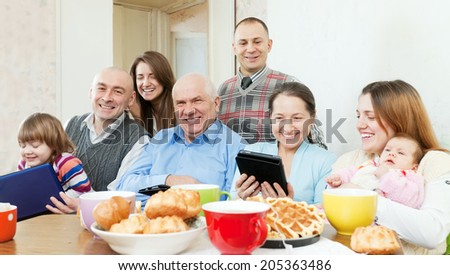 Happy family of three generations with electronic devices over tea in living room at home