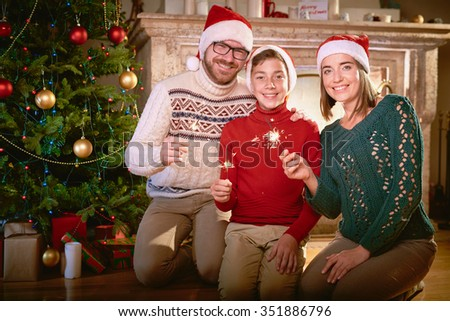 Happy family of three holding bengal lights and looking at camera by Christmas tree - stock photo