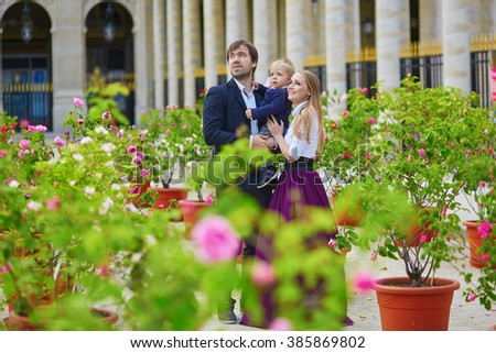 Happy family of three in the beautiful garden of Palais Royal in Paris on a summer day