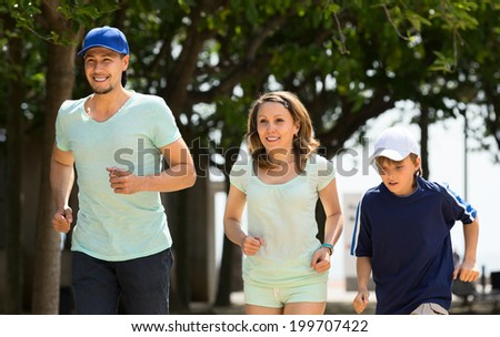 Happy family of three jogging in summer morning - stock photo