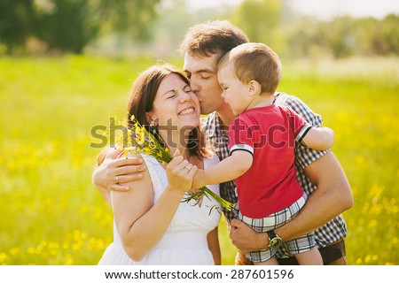 Happy family of three kissing outside. Mother in expectation of baby. Smiling faces of woman, man and child. Baby playing outdoors with parents. Togetherness. Man and woman hugging in sunset time. - stock photo