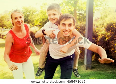 happy family of three looking happy and holding thumbs up in park on summer day 