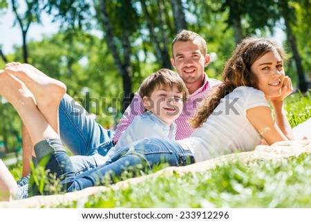 Happy family of three lying in summer park
