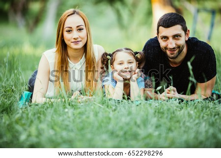 Happy family of three lying on grass. happy family relations and carefree leisure time