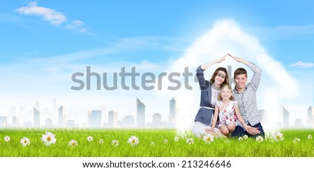 Happy family of three lying on green grass