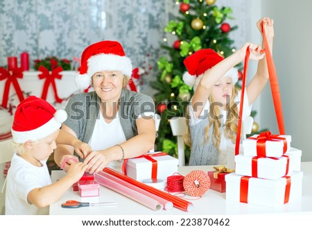 Happy Family of three, mom with children wrapping Christmas gifts at home, with Santa Hats and decorated Christmas Tree. - stock photo