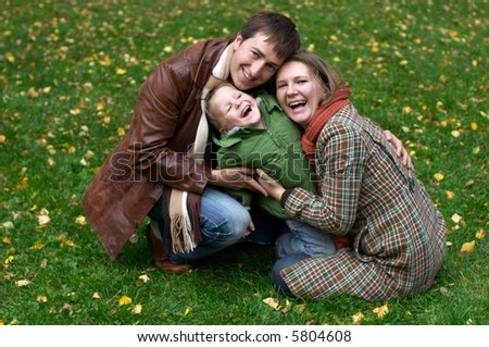 Happy family of three on the grass covered with fallen leaves
