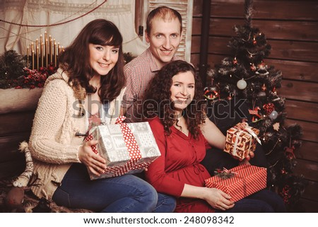 happy family of three people in a cozy rustic interior Christmas