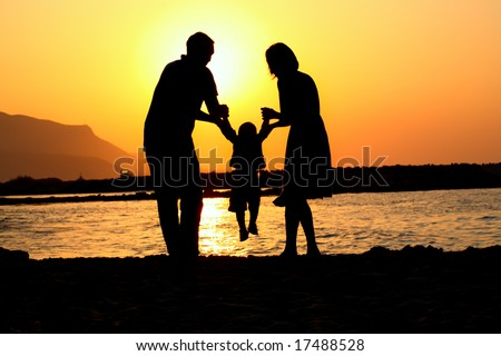 happy family of three playing silhouette - stock photo