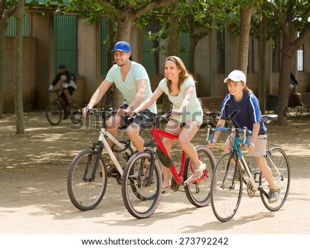 Happy family of three riding bikes in summer day - stock photo