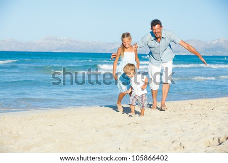 Happy family of three running and having fun on tropical beach - stock photo