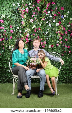 Happy family of three sit on bench with bunch of flowers in garden near verdant hedge. - stock photo