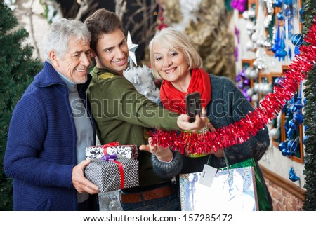 Happy family of three taking selfportrait through cellphone at Christmas store - stock photo
