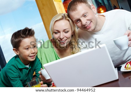 Happy family of three using a laptop while having lunch - stock photo