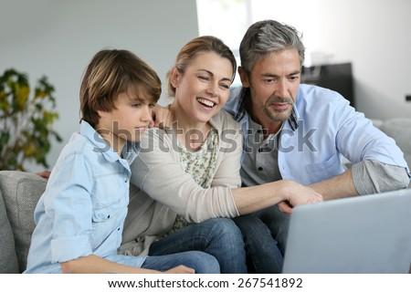 Happy family of three waving at camera during video call - stock photo