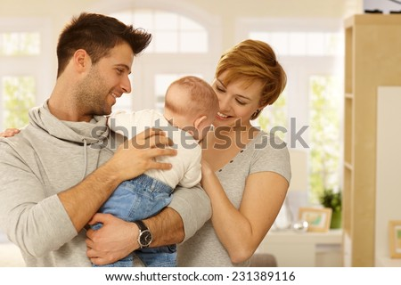 Happy family of three with little baby. - stock photo
