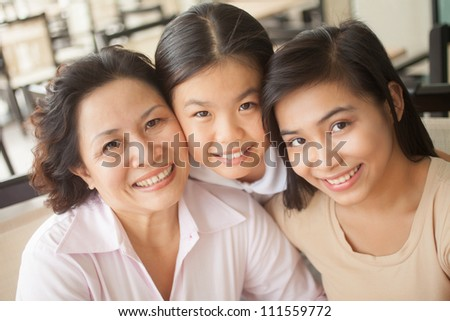 Happy family of three women embracing each other outdoors - stock photo