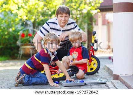 Happy family of three: young father and two little sibling boys reparing broken bicycle, outdoors. Selective focus
