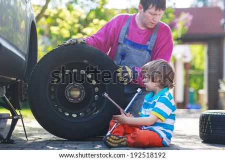 Happy family of two: father and adorable little preschool boy repairing car and changing wheel together on warm day, outdoors. - stock photo