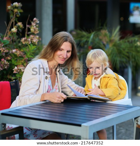 Happy family of two, mother, attractive young woman and her daughter, adorable toddler girl enjoying lunch at a beautiful outside cafe choosing meal from menu card on a sunny early autumn day - stock photo