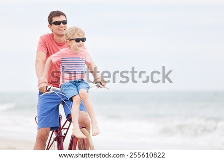happy family of two riding bicycle, having fun and enjoying vacation together - stock photo