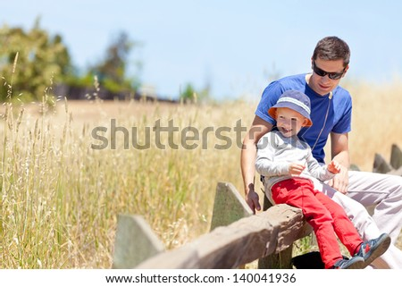 happy family of two spending time together; adorable smiling son enjoying summertime with his father at the park - stock photo