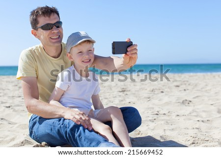 happy family of two taking picture at the beach, social media concept - stock photo
