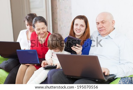 Happy family of with portable computers on sofa at home