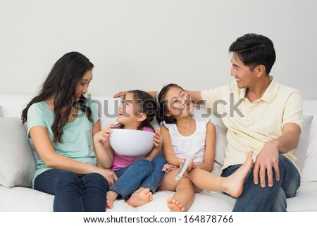 Happy family of with remote control and bowl sitting on sofa in the living room at home - stock photo