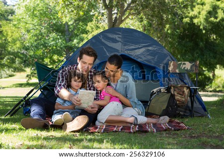 Happy family on a camping trip in their tent on a sunny day - stock photo