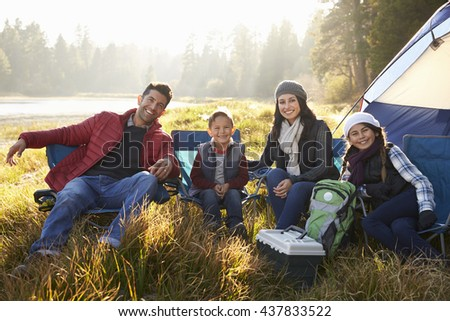 Happy family on a camping trip sit by tent looking to camera - stock photo