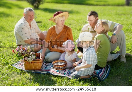 Happy family on a glade in park - stock photo