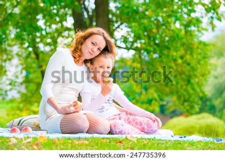 happy family on a picnic snack apples in the park - stock photo