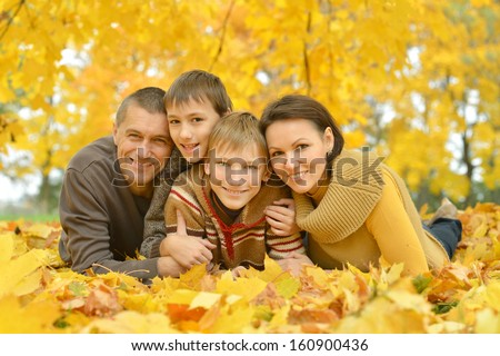 happy family on a walk during the fall of the leaves in the park