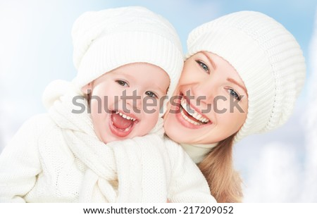 happy family on a winter walk. Mother and baby daughter in the white hats laughing - stock photo