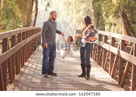 Happy family on a wooden bridge swinging their daughter - stock photo