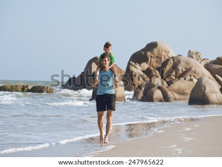 happy family on beach playing, father with son walking sea coast, rocks behind - stock photo