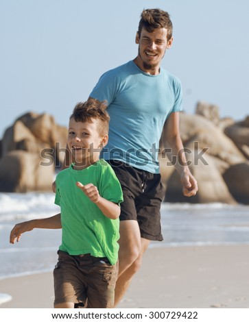happy family on beach playing, father with son walking sea coast, rocks behind smiling enjoy summer vietnam