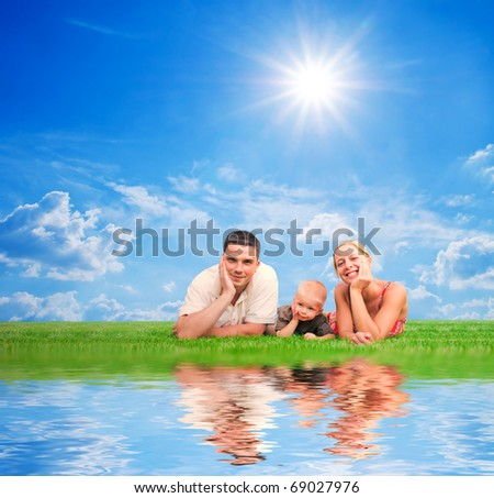 Happy family on grass, sunny sky. Mother, father and a child. - stock photo