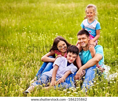 Happy family on green grass. Outdoor. - stock photo
